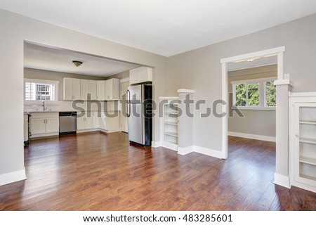 Open floor plan. White kitchen room interior with marble counter top and hardwood floor. Northwest, USA
