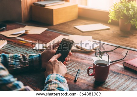 Open for communication. Close-up image of man holding smart phone while sitting at the rustic wooden table  - stock photo