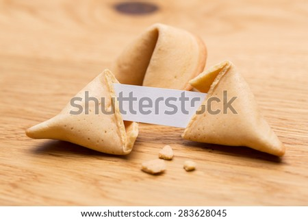 open fortune cookie with crumbs and note on wooden table - stock photo