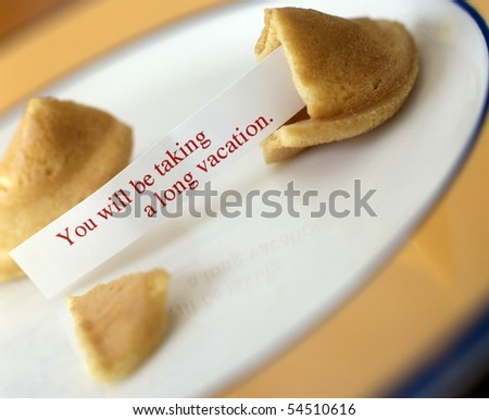 Open Fortune Cookie with Saying laying on plate - stock photo