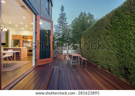Open french doors leading into contemporary home with wooden terrace, open floor plan, greenery at night. Large window showing modern interior at twilight.  - stock photo