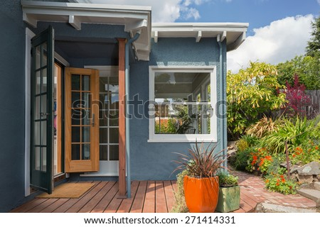 Open french doors with wooden deck and amazing flower pots in sky blue home. - stock photo