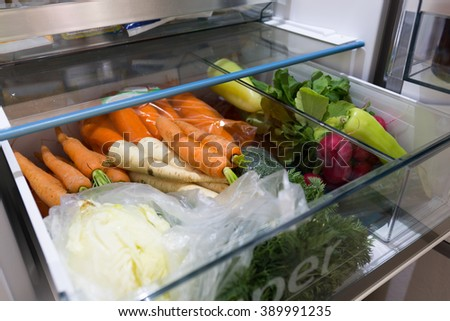 Open fridge filled with vegetables - stock photo
