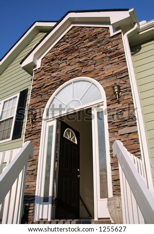Open front door of a home with a stone facade. - stock photo