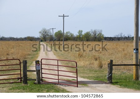 Open gate and lonely little road lead to a family farm on the horizon.  There is a no-trespassing sign on the post to the right. - stock photo