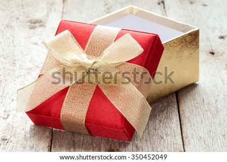Open gift box on the old wooden floor - stock photo