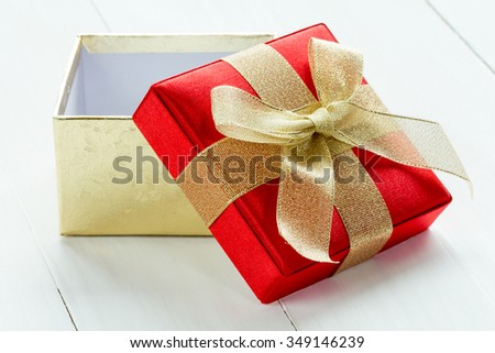 Open gift box on the white wooden background - stock photo
