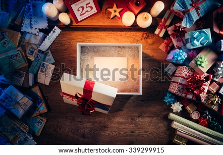 Open gift box with a blank white card inside, presents and Christmas letters all around, desktop top view - stock photo