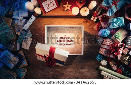 Open gift box with a Merry Christmas and Happy New Year message, presents and Christmas letters all around, desktop top view - stock photo
