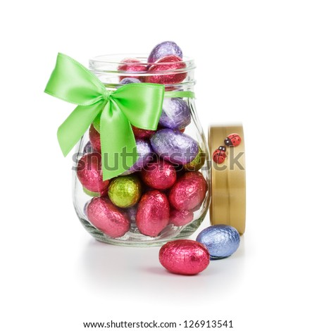 Open glass jar full of chocolate candy Easter eggs wrapped in foil decorated with bow and ladybugs clipping path included - stock photo