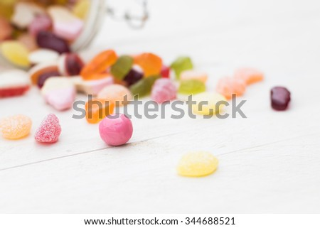 Open glass jar full of different colourful jelly candies on white wooden background - stock photo