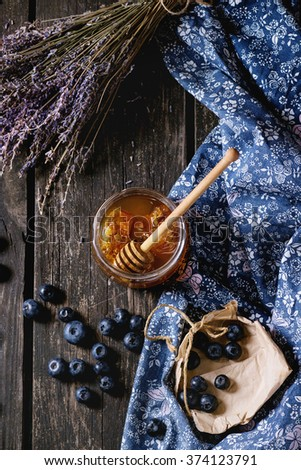Open glass jar of liquid honey with honeycomb and honey dipper inside, fresh blueberries and bunch of dry lavender over old wooden table with blue textile rag. Dark rustic style. Flat lay - stock photo