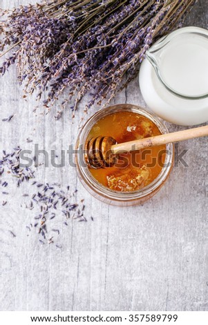 Open glass jar of liquid honey with honeycomb and honey dipper inside, glass jug of milk and bunch of dry lavender over white wooden surface Rustic style. Top view - stock photo