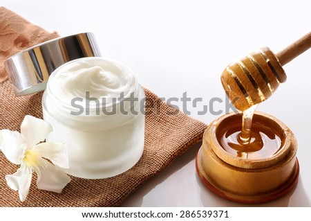 Open glass pot with honey moisturizer isolated on white glass table.  Flower, burlap and cane with honey container decoration. Top view - stock photo