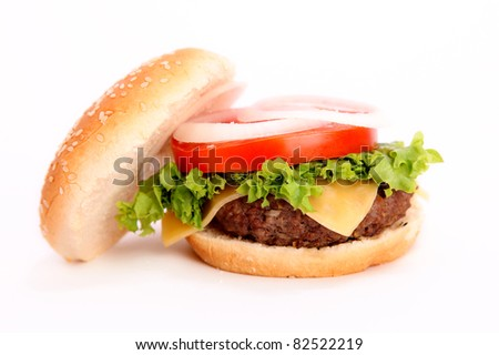 open hamburger with onion,tomato,lettuce,cheese,meat and bread over white background - stock photo