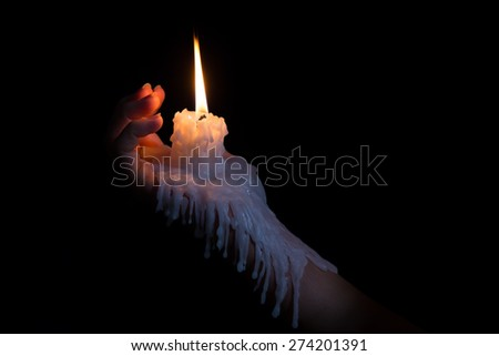 Open hand holding a candle stick with wax flowing down the arm - stock photo