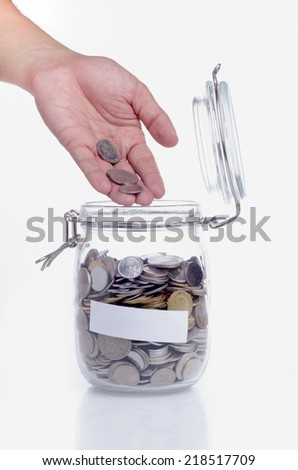 Open hand putting coin into the glass jar with coin - stock photo
