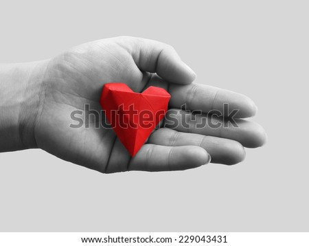 Open hands and red origami heart. The concept of love or health insurance. - stock photo