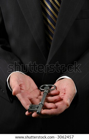 Open hands holding a key representing endless possibilities. - stock photo