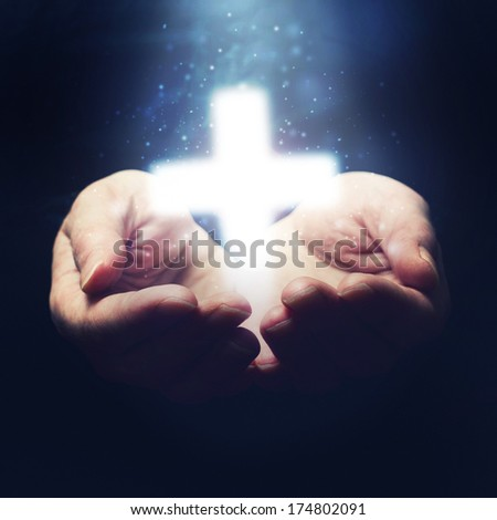 Open hands holding cross, symbol of Christian faith. Religion and spirituality concept. - stock photo