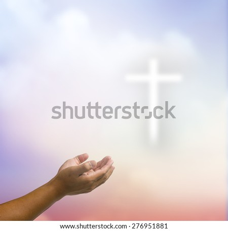 open hands praying the cross on blur sky background. - stock photo