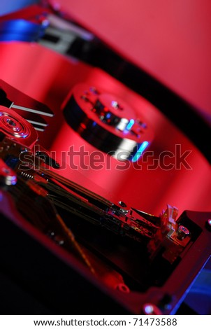 Open hard disk close-up with electronics in the background - stock photo