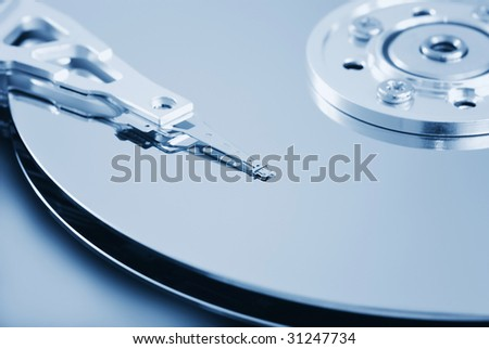 Open hard disk drive - shallow depth of field with focus on the head (toned in light blue) - stock photo