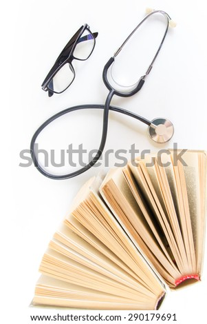 Open hardback books on the table, stethoscope and glasses. Medical professional education and information concept. Back to school, copy space. - stock photo