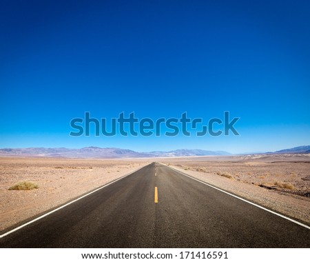 Open highway beckoning the desert and mountains of Death Valley in California. - stock photo
