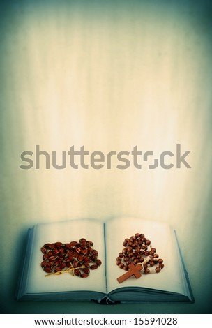 open holy book and rosary on abstract retro background - stock photo