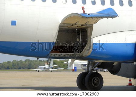 Open hydraulically operated cargo compartment door of an airplane at the airport