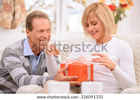 Open it. Pleasant vivacious nice adult couple holding present and celebrating St Valentine day while expressing love - stock photo