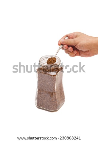 Open jar with instant coffee and hand with  spoon  - stock photo