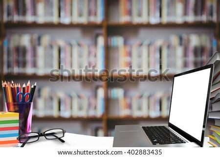 Open laptop against library shelf - stock photo