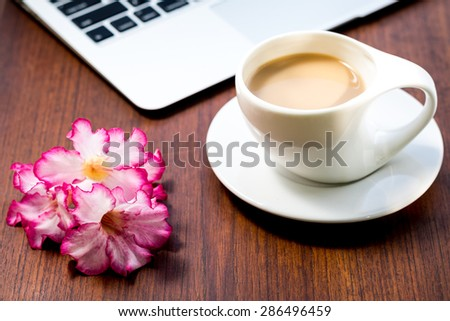 Open laptop and cup of coffee on brown wooden table.  - stock photo