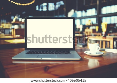 Open laptop computer and cup of coffee lying on a wooden table in cafe bar interior, portable net-book with copy space screen for your information content or text message, freelance work via internet - stock photo