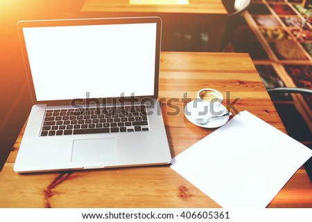 Open laptop computer and sheet of paper with copy space for your text message on advertising content, net-book and cup of coffee lying on wooden table in contemporary interior, education via internet  - stock photo