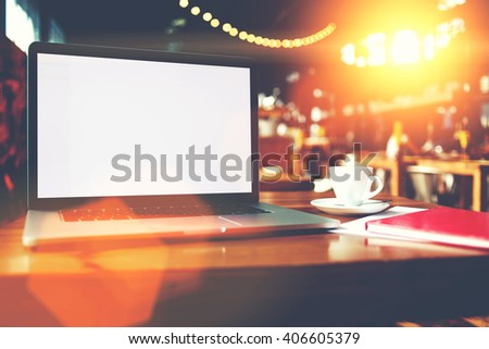 Open laptop computer with blank copy space screen for information content or text message,portable net-book and cup of drink lying on table in contemporary coffee shop interior, freelance workspace - stock photo