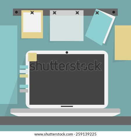 Open laptop on a desk and background wall with pinned papers and a card - stock photo