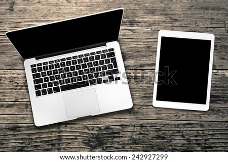 Open laptop with digital tablet. All with isolated screen on old wooden desk.  - stock photo