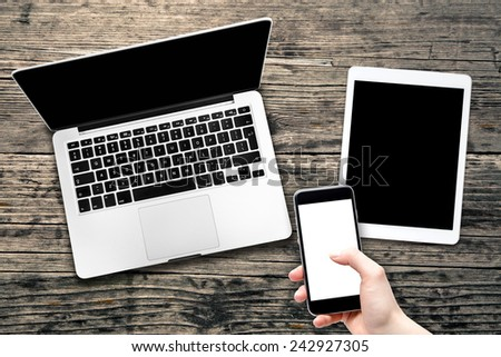 Open laptop with digital tablet and smartphone in hand. All with isolated screen on old wooden desk.  - stock photo
