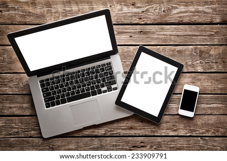 Open laptop with digital tablet and white smartphone. All with isolated screen on old wooden desk. - stock photo