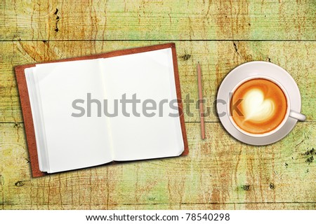 Open leather covered  book with blank page, coffee and pencil on old wooden floor - stock photo