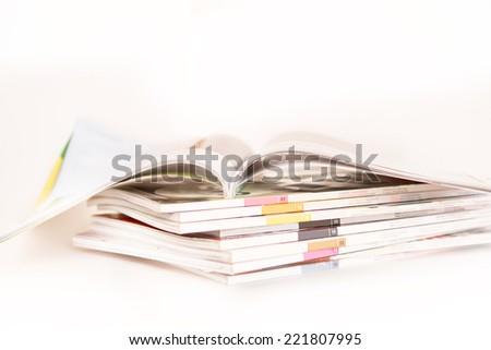 Open Magazine on stack of magazines - stock photo