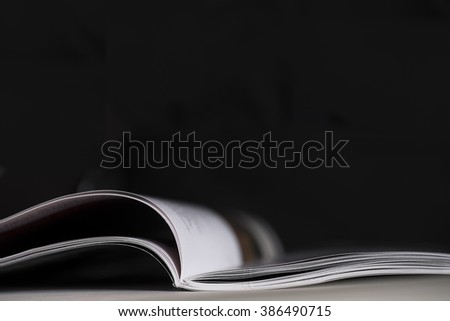 Open magazine with with shallow depth of field with black background