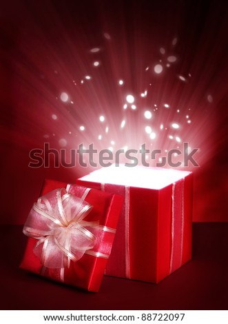 Open magic gift box on red background - stock photo