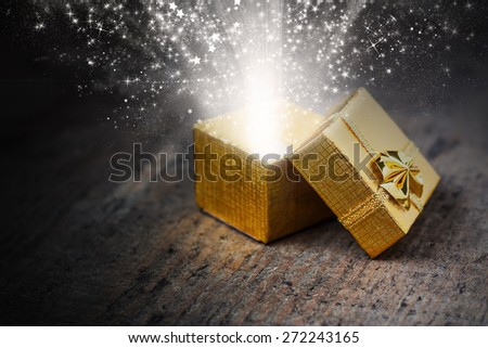 Open magic gift with rays and sparks close-up on a wooden surface - stock photo