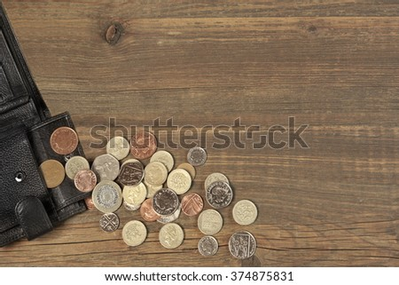 Open Male Black Leather Wallet With British Different Coins On Old Rustic Rough Brown Wood Background With Copy Space, Overhead View - stock photo