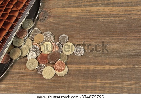 Open Male Brown Leather Wallet With British Different Coins On Old Rustic Rough Brown Wood Background With Copy Space, Overhead View - stock photo