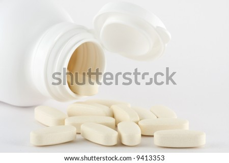 Open medicine flask with pills on white background